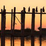 Silhouette of three monks on the U Bein bridge at sunset, Bura
