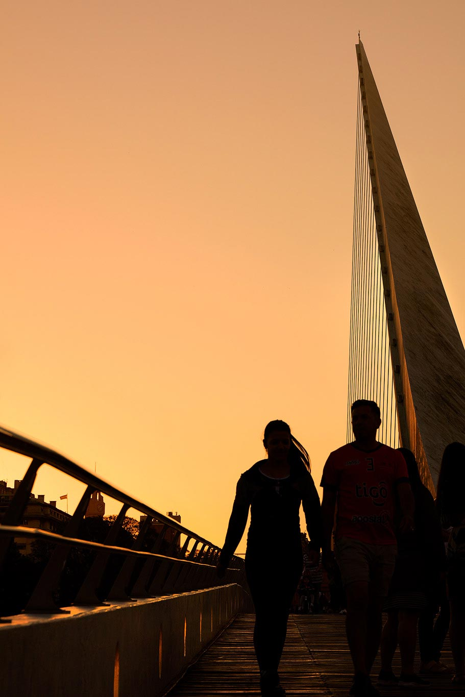 People walking on the Puente de la Mujer at sunset