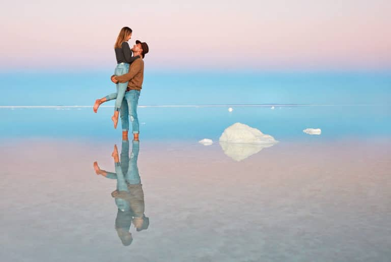 Couple reflected in the Uyuni waters at twilight